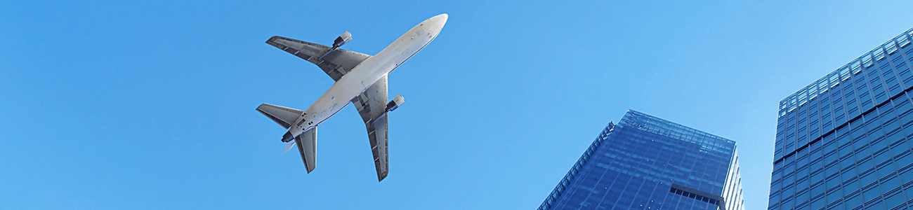A jumbo jet airplane flying over skyscrapers. Clear blue sky behind.